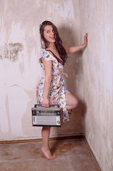 Pin up foto der altmodischen jungen frau mit dem alten radio mit dem breiten lächeln