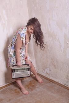Pin up foto der altmodischen jungen frau mit dem alten radio