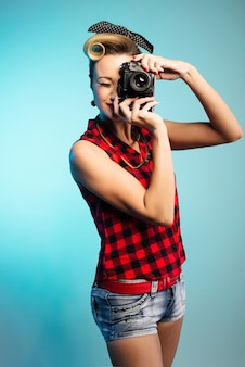 Pin up frau macht fotos mit vintage-kamera