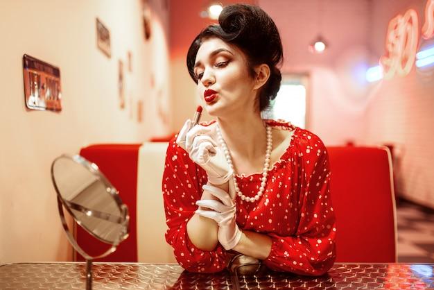 Pin-up-frau mit hellem lippenstift in der hand sitzen gegen spiegel, kleid mit tupfen, vintage-stil. retro cafe 50 amerikanische mode