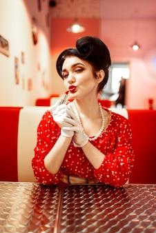 Pin-up-frau mit hellem lippenstift in der hand