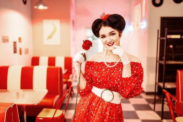 Pin-up-frau mit make-up hält rote rose, kleid mit tupfen, vintage-stil. retro cafe interieur mit schachbrettboden