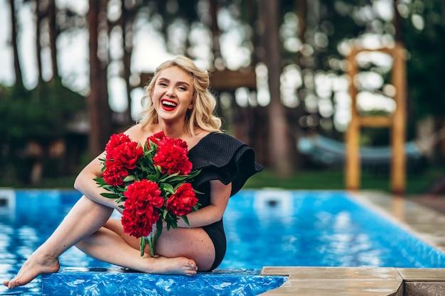 Pin up gestylte blondine im schwarzen vintage-badeanzug, der im pool im freien entspannt