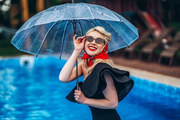 Pin up gestylte blondine in sonnenbrille mit regenschirm und viel spaß im schwimmbad