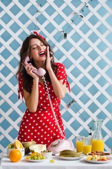 Pin-up-girl in einem roten kleid am telefon sprechen. saftige farben
