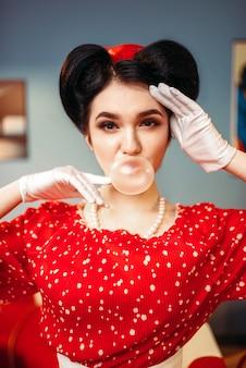 Pin-up-girl mit make-up bläst den kaugummi auf