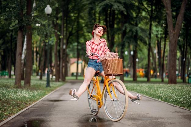 Pin-up-mädchen auf retro-fahrrad, vintage amerikanische mode. nette frau im pinup-stil