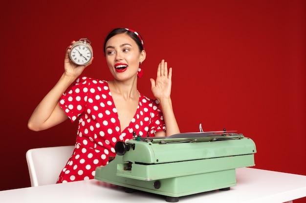 Pin up mädchen, das auf einer schreibmaschine tippt