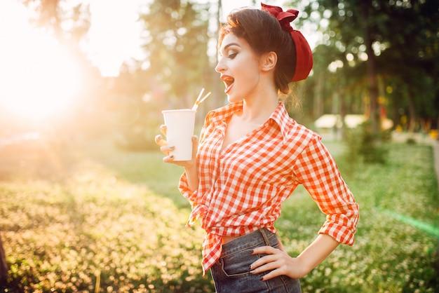 Pin up mädchen hält pappbecher mit einem strohhalm, stadtpark auf hintergrund. vintage amerikanische mode. attraktive frau im pinup-stil