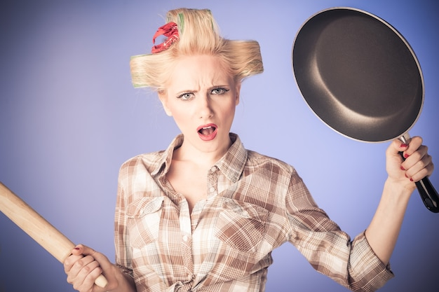 Pin-up-mädchen jahrgang. schönes frauenporträt im pinup-stil in retro-kleid und küchenutensilien