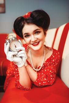 Pin-up-mädchen mit wecker in der hand posiert im vintage-café, beliebte amerikanische mode 50er und 60er jahre. rotes kleid mit tupfen