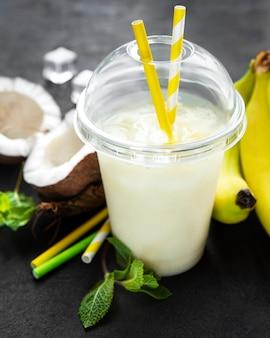 Pina colada alkoholischer frischer cocktail serviert kalt mit kokosnuss und banane auf einem schwarzen hintergrund