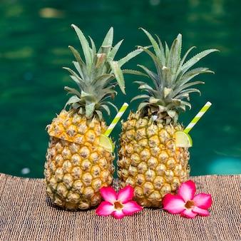 Pina colada cocktail in frischen zwei ananas nahe schwimmbad