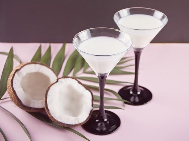 Pina colada-cocktail mit palmblatt und kokosnuss auf dem hintergrund