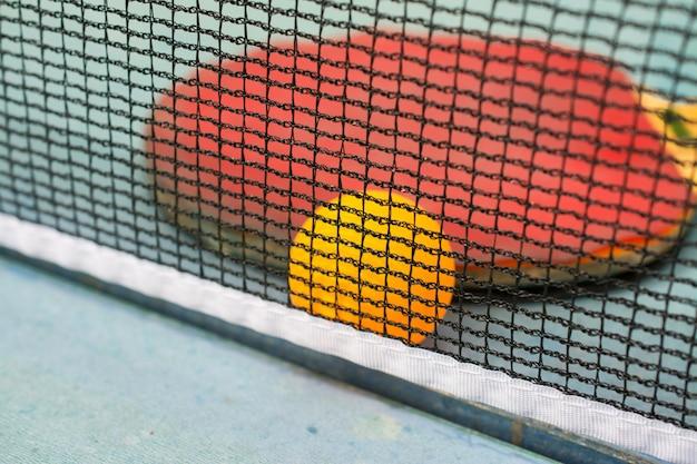 Ping pong paddel und ball auf retro blau holz hintergrund. von der zeit zerstörte schläger