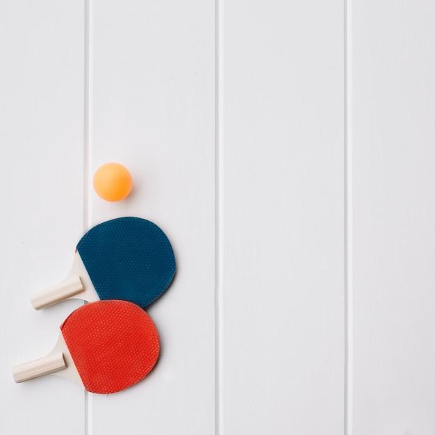Ping-pong-schläger zwei und ball über weißem hölzernem hintergrund mit raum