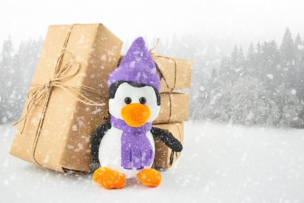 Pinguin mit geschenken auf einem winterhintergrund mit kopienraum. weihnachtshintergrund. banner.
