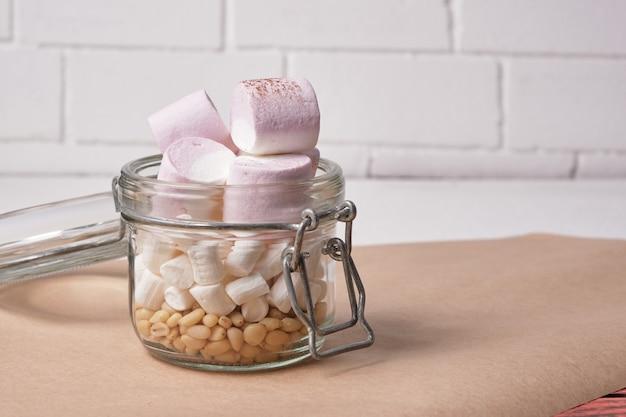 Pinienkerne und marshmallows im glas auf dem tisch