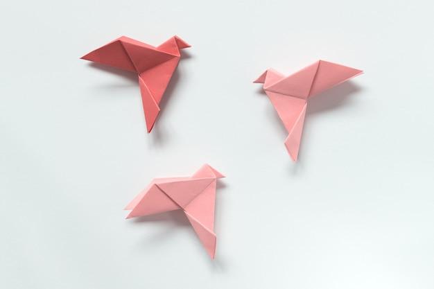 Pink birds in verschiedenen farben. origami. das konzept der freiheit, inspiration.