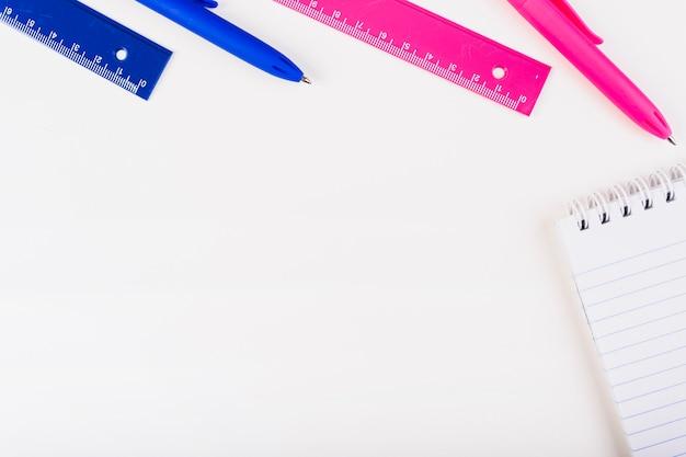 Pink-blaue stifte und lineale mit notizblock