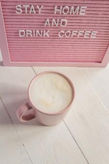 Pink coffee tasse und qoute bleib zu hause und trink kaffee. selbstisolations- und quarantänekampagne, um sich selbst zu schützen