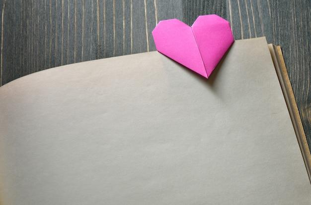 Pink lesezeichen ein herz aus origami. hintergrund für design am valentinstag