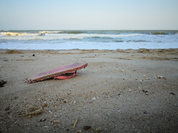 Pink slipper müll wäscht sich am strand.