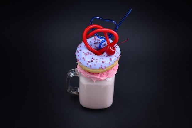 Pinker erdbeer-freakshake mit marshmallow und süßigkeiten.
