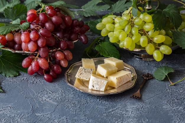 Pinsel aus roten trauben in einem silbernen teller und ein pinsel aus hellen trauben, eine rebe, käse in einem silbernen teller und eine gabel