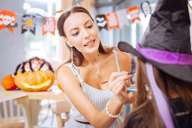 Pinsel für gesicht. schöne frau mit nettem make-up, das pinsel hält, während gesicht des mädchens malt, das für halloween bereit ist