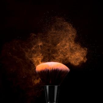 Pinsel für make-up im puder sprengte auf dunklem hintergrund