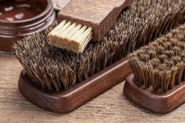 Pinsel für schuhe. schuhe mit bürsten reinigen und polieren. schuhcreme und pinsel auf holzhintergrund.