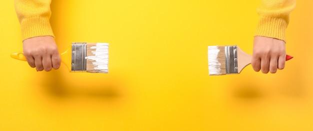 Pinsel in der hand eines mädchens auf gelb