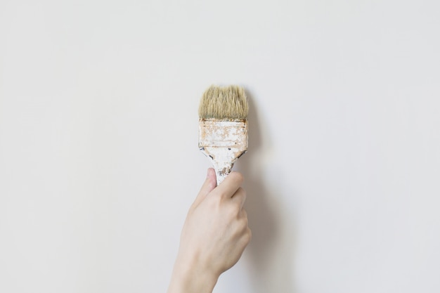 Pinsel in der hand eines mannes. prozesskonzept. mann malerei wand