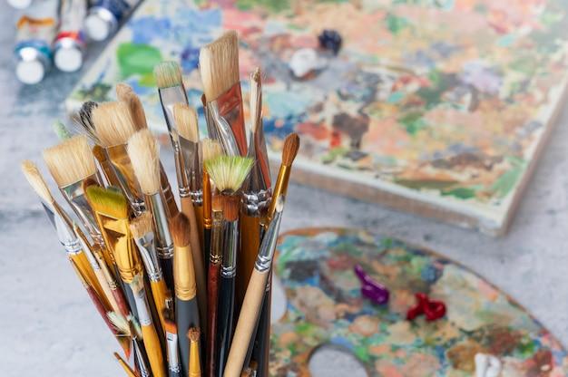 Pinsel in einer glasnahaufnahme auf dem hintergrund einer palette, der farben und der leinwand.