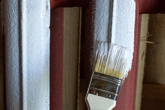 Pinsel in weißer farbe befleckt die eisenbatterie.
