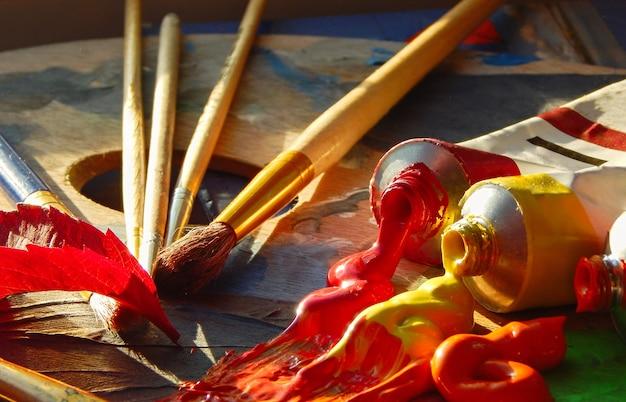Pinsel, künstlerpalette, ölfarben auf dem schreibtisch im malerstudio.
