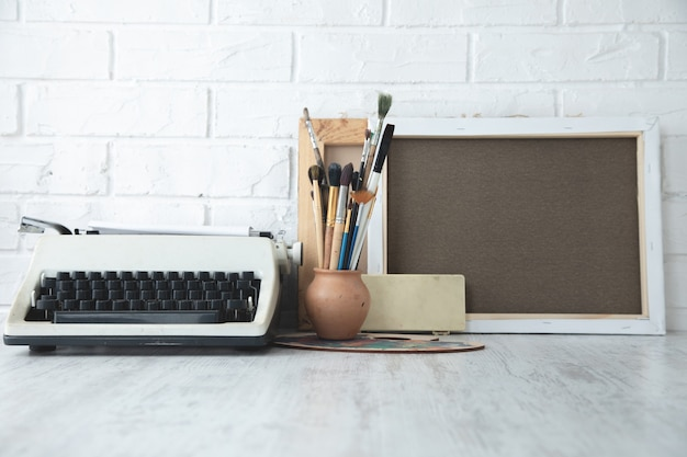 Pinsel, leinwand und alte schreibmaschine auf dem schreibtisch