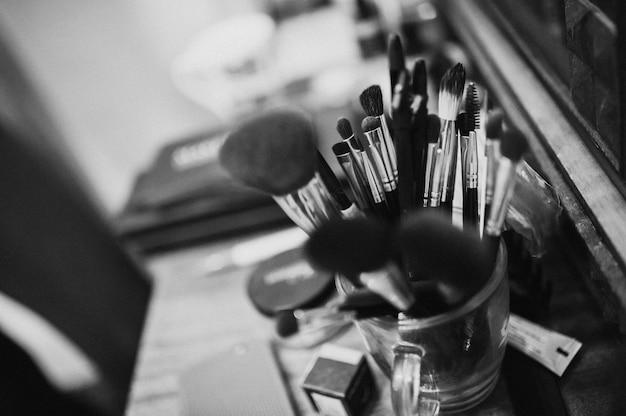 Pinsel maskenbildner. maskenbildner am arbeitsplatz. schwarzweiss-foto. hochzeitsvorbereitungen. morgen der braut. hochzeits make-up.