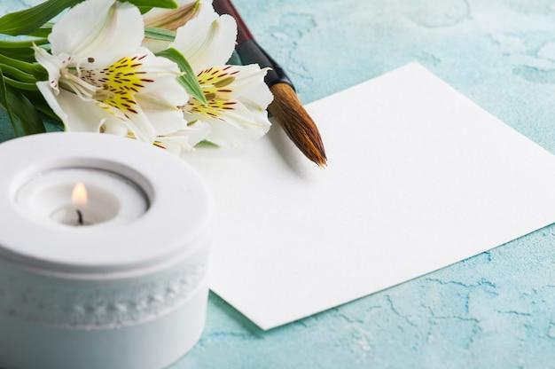 Pinsel mit brennender kerze, papier, blüten