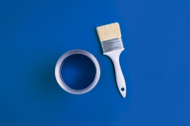 Pinsel mit einer offenen farbdose auf trendigem classic blue hintergrund. farbe des jahres 2020.