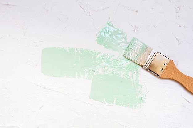 Pinsel mit farbfarbe auf weißem wandhintergrund