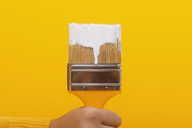 Pinsel mit weißer farbe in der hand