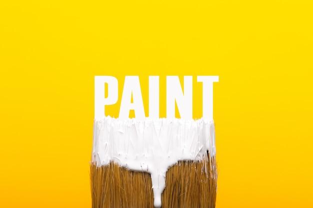 Pinsel mit weißer farbe über gelbem hintergrund, reparatur- und malwerkzeugkonzept
