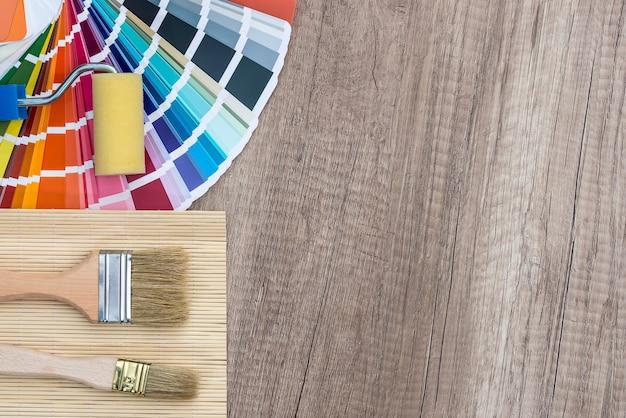 Pinsel und farbfelder auf holztisch malen