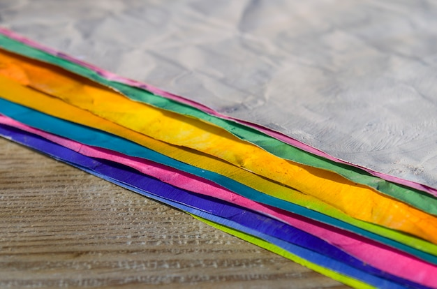Pinsel und farbiges papier auf hölzernem hintergrund. kunst hintergrund. kunstbedarf