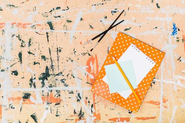 Pinsel und notizbücher auf abstraktem hintergrund