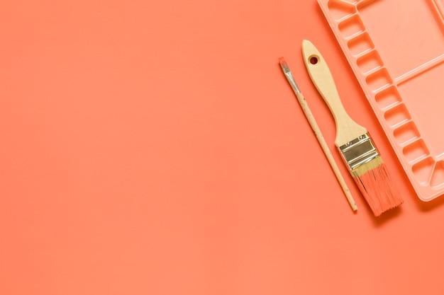 Pinsel und palette auf rotem hintergrund