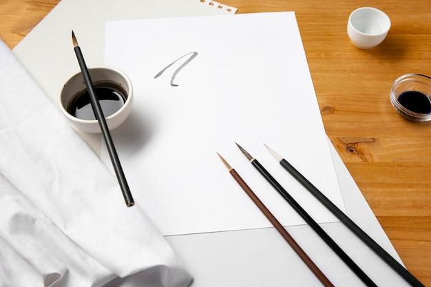 Pinsel und schwarze tinte auf papier