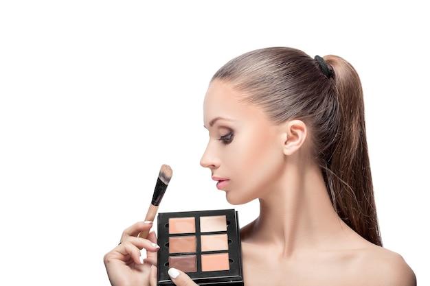 Pinsel zum formen des gesichts. natürliches make-up für die perfekte haut. der maskenbildner macht make-up mit pinsel.
